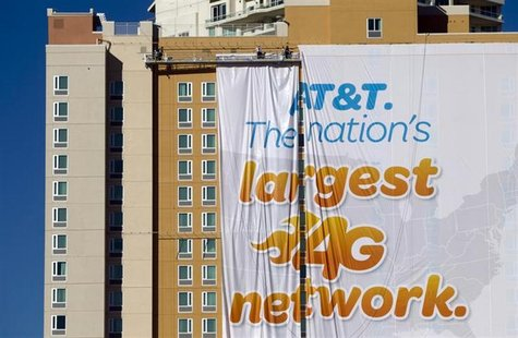 Workers put up a banner advertisement for AT&T on the side of a hotel as they prepare for International CES show in Las Vegas, Nevada Januar