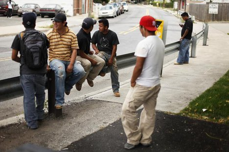 A group of immigrant day laborers stand near a street corner waiting for work in the Staten Island borough of New York August 3, 2010. REUTE