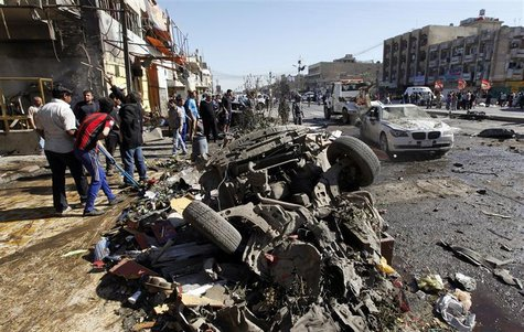 Residents gather at the site of a car bomb attack in the AL-Mashtal district in Baghdad March 19, 2013. A series of coordinated car bombs an