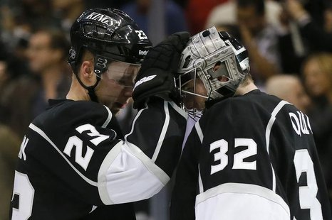 Los Angeles Kings captain Dustin Brown (L) celebrates with teammate goaltender Jonathan Quick after they defeated the Calgary Flames during