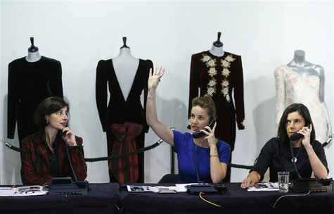 A worker takes telephone bids during the auction of ten dresses worn by Britain's Princess Diana, at Kerry Taylor Auctions in London March 1