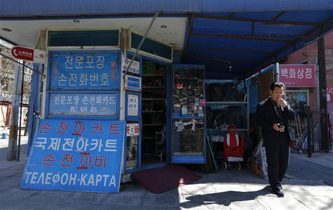 A North Korean uses a mobile phone next to a shop with a signboard written in Korean characters near the North Korean embassy in Beijing Mar