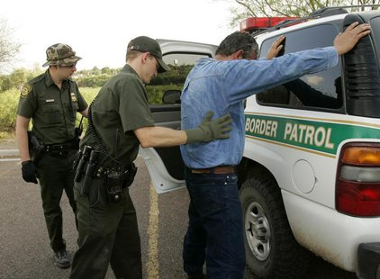 Border Patrol Agent David Perkins (C) searches an undocumented immigrant from Mexico he detained, after the man was caught coming into Lared