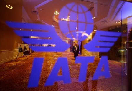 A delegate of the 68th International Air Transport Association (IATA) annual general meeting is pictured through an IATA logo in Beijing Jun
