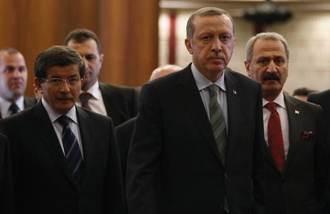 Turkey's Prime Minister Recep Tayyip Erdogan arrives for a news conference as he is flanked by Foreign Minister Ahmet Davutoglu (L), Economy