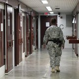A guard walks through a cellblock inside Camp V, a prison used to house detainees at Guantanamo Bay U.S. Naval Base, March 5, 2013. REUTERS/