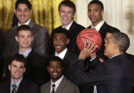 President Barack Obama holds a ball as he welcomes the University of Kentucky men's basketball team to the White House in Washington to cele