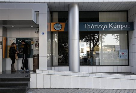 People make transactions at an ATM outside a branch of Bank of Cyprus in Nicosia March 20, 2013. REUTERS/Yorgos Karahalis