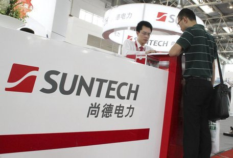 An employee (L) talks to a visitor at the Suntech booth of a photovoltaic industry exhibition in Beijing, September 5, 2012. REUTERS/Stringe