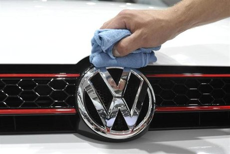A man polishes the Volkswagen logo on a vehicle at an exhibition which is part of the annual shareholders meeting of Volkswagen AG in Hambur
