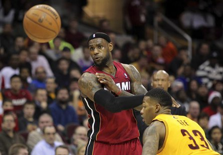Miami Heat's LeBron James (L) passes the ball past Cleveland Cavaliers defender Alonzo Gee (33) during the third quarter of their NBA basket