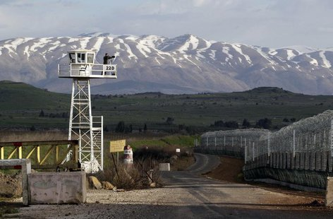 A United Nations peacekeeper stands on an observation tower at the Kuneitra border crossing between Israel and Syria, in the Israeli occupie