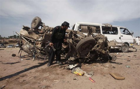 A security official inspects a damaged vehicle at the site of a bomb attack nearJalozai camp in Nowshera district, northwestern Pakistan Mar
