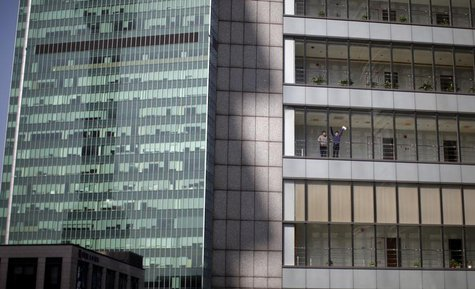 Men chat outside of an office of the Bocom Financial Tower at Pudong financial district in Shanghai March 21, 2013. REUTERS/Carlos Barria