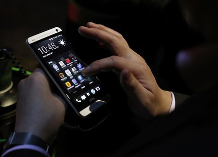 An attendee tests the new HTC One during a launch event in New York, February 19, 2013. REUTERS/Brendan McDermid