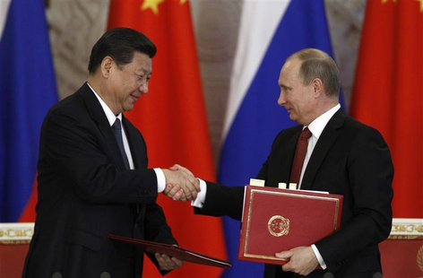 Russia's President Vladimir Putin (R) exchanges documents with his Chinese counterpart Xi Jinping during a signing ceremony at the Kremlin i