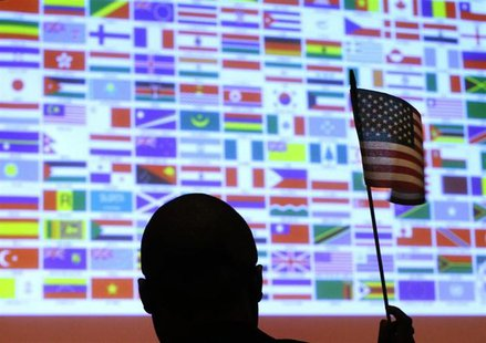 A new U.S. citizen waves a U.S. national flag in front of a display of flags of the more than 40 nations represented by the more than 90 imm