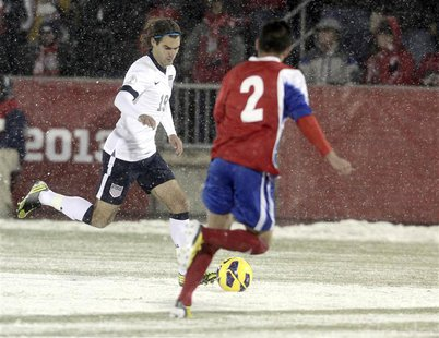 Graham Zusi of the U.S. (L) races past Costa Rica's Christian Gamboa (R) with the ball during their 2014 World Cup qualifying soccer match i