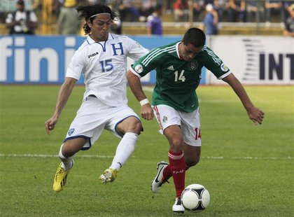 Mexico's Javier Hernandez (R) controls the ball past Honduras' Roger Espinoza during their 2014 World Cup qualifying soccer match at Olimpic