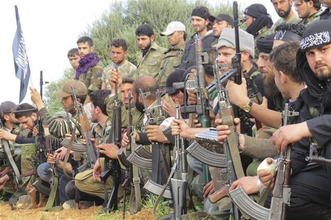 Free Syrian Army fighters carry their weapons as they sit in attention during the declaration of the formation of Al-Liwaa brigade in Binnis