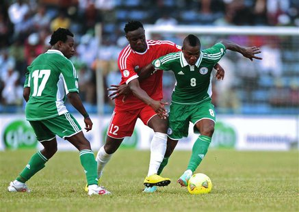Kenya's Victor Wanyama (C) challenges Nigeria's Brown Ideye (R) during their 2014 World Cup qualifying soccer match at the U.J Esuene Stadiu