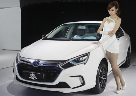 A model stands next to China's BYD QIN at Auto China 2012 in Beijing April 24, 2012. REUTERS/Jason Lee