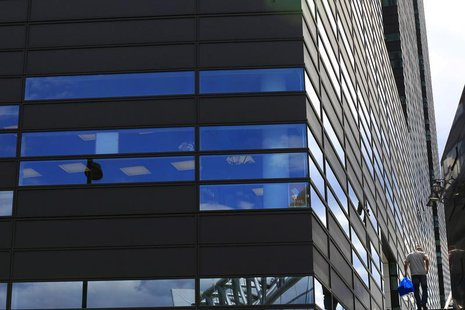 An office worker climbs steps beside a new office development on the waterfront in Oslo, Norway June 20, 2012. REUTERS/Cathal McNaughton