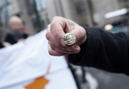 A man holds a broken 1-euro coin pin during a protest comprising of around 40 people from Cyprus, outside a Eurogroup meeting at the Europea