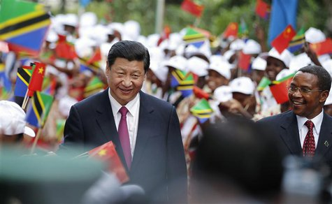 China's President Xi Jinping (L) and his Tanzanian counterpart Jakaya Kikwete (R) walk through women waving China and Tanzania national flag