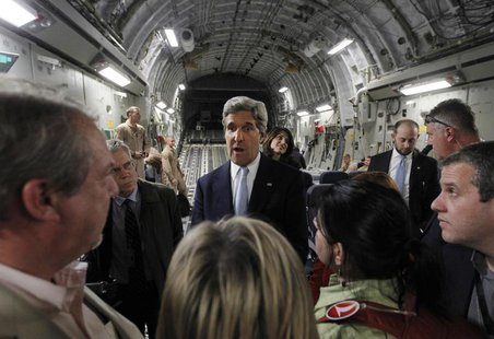 U.S. Secretary of State John Kerry (C) speaks to the media on an Air Force C-17 aircraft upon his return to Amman from a trip to Baghdad Mar