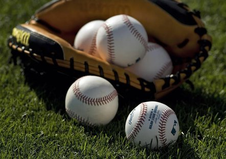 Baseballs and a catcher's mitt lie on the grass before a MLB spring training baseball game between the Boston Red Sox and Baltimore Orioles