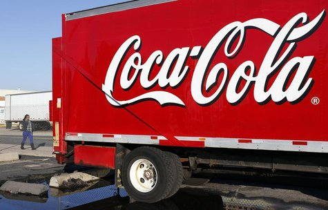 A woman walks past a Coca-Cola truck truck at a distribution center in Alexandria, Virginia October 16, 2012. REUTERS/Kevin Lamarque