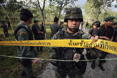 Security personnel investigate at the site of an attack on an army base near Bacho in the troubled southern province of Narathiwat February