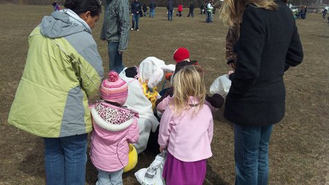 Easter Bunny stoops to help make sure child doesn't leave the field without an egg.