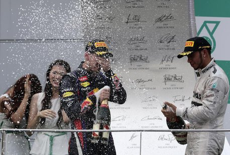 Third placed Mercedes Formula One driver Lewis Hamilton (R) of Britain sprays champagne at winner Red Bull Formula One driver Sebastian Vett