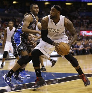 Miami Heat forward LeBron James (R) drives as he is defended by Orlando Magic forward Maurice Harkless (L)during the first half of their NBA