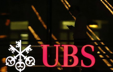 An employee uses a mobile phone as he walks past the logo of Swiss bank UBS in Zurich December 17, 2012. REUTERS/Michael Buholzer