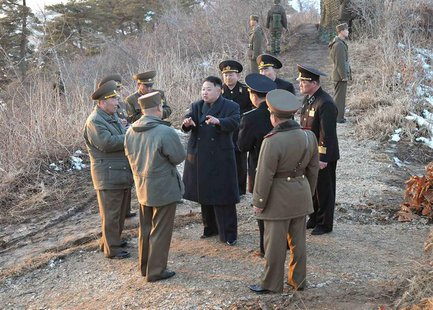North Korean leader Kim Jong-Un (C) talks with generals as soldiers of the Korean People's Army (KPA) take part in the landing and anti-land