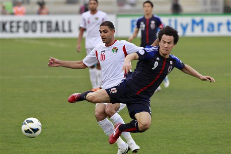 Japan's Shinji Okazaki (R) fights for the ball against Jordan's Basem Othman during their 2014 World Cup qualifying soccer match at King Abd