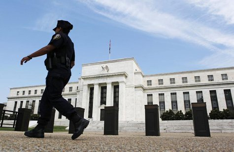 A police officer walks in front of the Federal Reserve, which is expected to release minutes of Federal Open Market Committee from August 1,