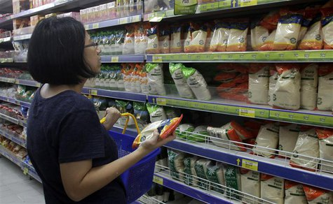 A woman examines the prices of white sugar displayed in a supermarket in Jakarta March 12, 2013. REUTERS/Supri