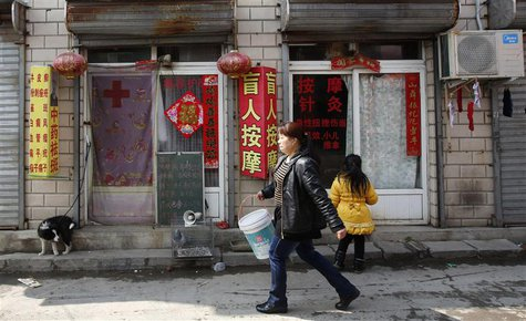Pedestrians walk past a shop (L) providing Chinese dermatologic treatment at a street market on the outskirts of Beijing March 20, 2013. REU