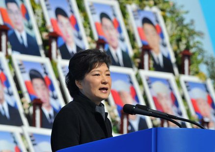 South Korea's President Park Geun-Hye speaks in front of photographs of sailors who died, during an event marking the third anniversary of t