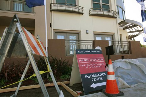 Construction equipment sits next to signs advertising new condominium homes for sale in South San Francisco, California, December 22, 2009.