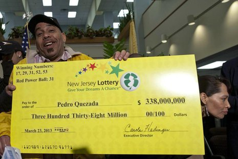 Pedro Quezada, winner of the Powerball lottery, holds up the promotional Powerball jackpot check of $338 million at the end of a news confer