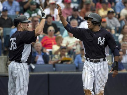 New York Yankees' Thomas Neal (R) celebrates with teammate Kevin Youkilis after scoring against the Boston Red Sox during the second inning
