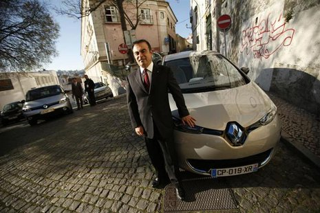 Carlos Ghosn, chairman and chief executive cfficer of French carmaker Renault, poses next to a Renault Zoe new electric car after a meeting