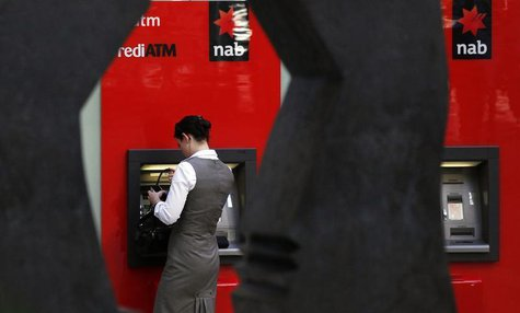 A woman uses a National Australia Bank (NAB) ATM in central Sydney May 5, 2011. REUTERS/Daniel Munoz