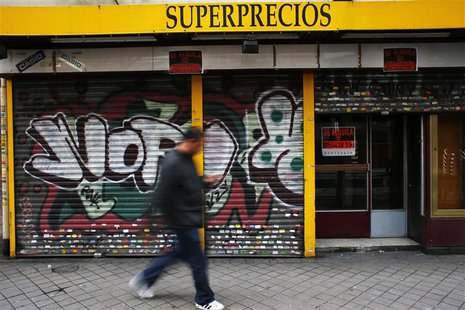 A man walks past a closed down business in Madrid March 27, 2013. REUTERS/Susana Vera
