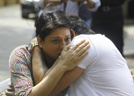 Bollywood actor Sanjay Dutt (R) embraces his sister Priya Dutt after breaking down during a news conference outside his residence in Mumbai